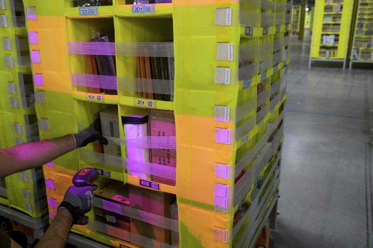 In this Dec. 5, 2018, photo Amazon Stower Leo Esparragoza uses colored light to help sort merchandise into pods at the Amazon fulfillment center on Staten Island borough of New York. Amazona€™s a€œPrime Daya€ is back. The made-up holiday, first launched in 2015, has become one of Amazona€™s busiest shopping days, offering discounts on gadgets, TVs and other goods. (AP Photo/Mary Altaffer)
