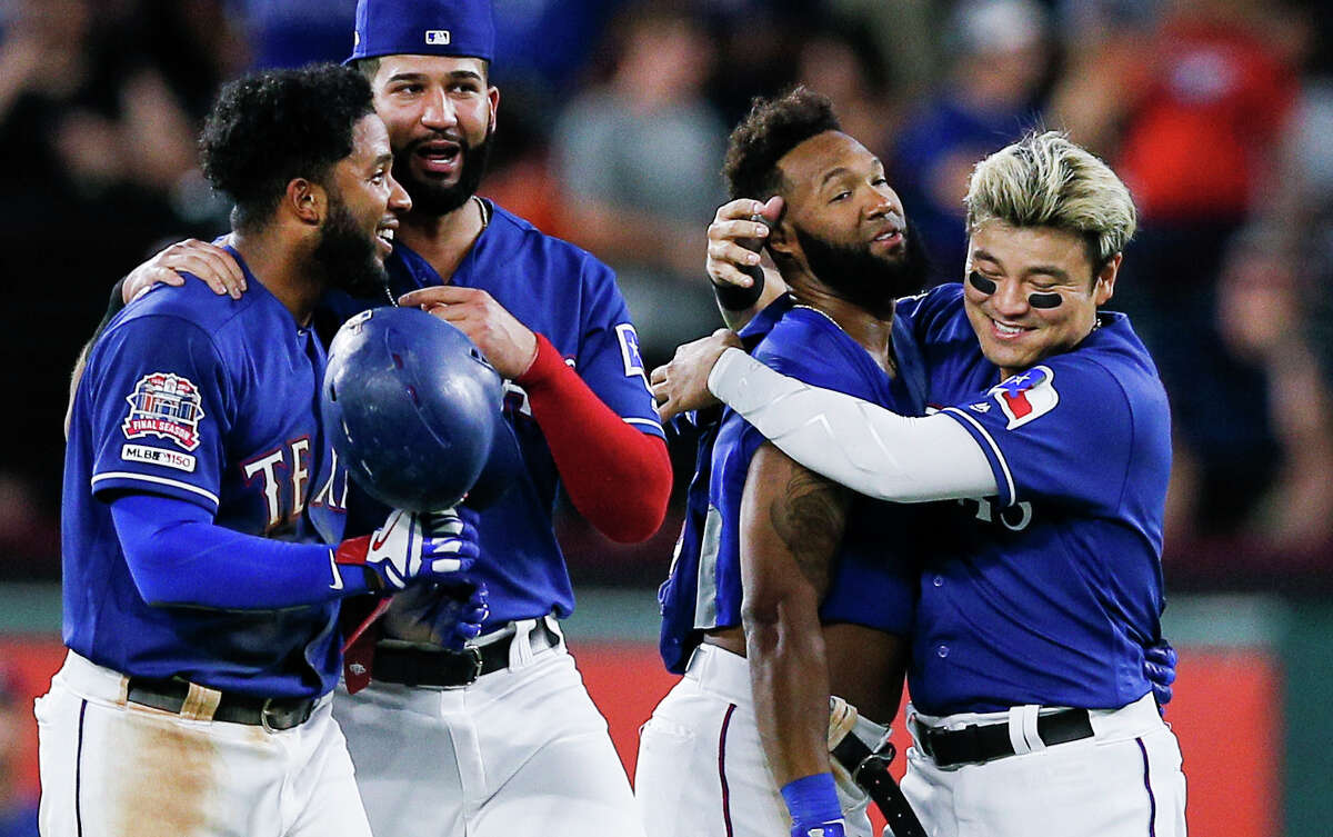Texas Rangers' Danny Santana, second from right, is congratulated by Shin-Soo Choo after hitting a walkoff single RBI to end a baseball game against the Houston Astros, Friday, July 12, 2019, in Arlington, Texas. (AP Photo/Brandon Wade)