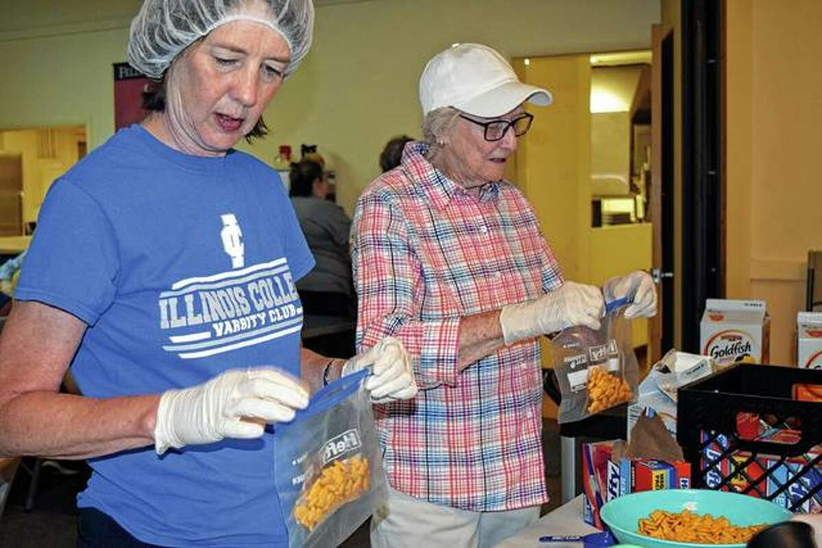 Janet Chipman (left) helps fill baggies with Goldfish crackers on Monday for the Take It to the Streets lunch program.