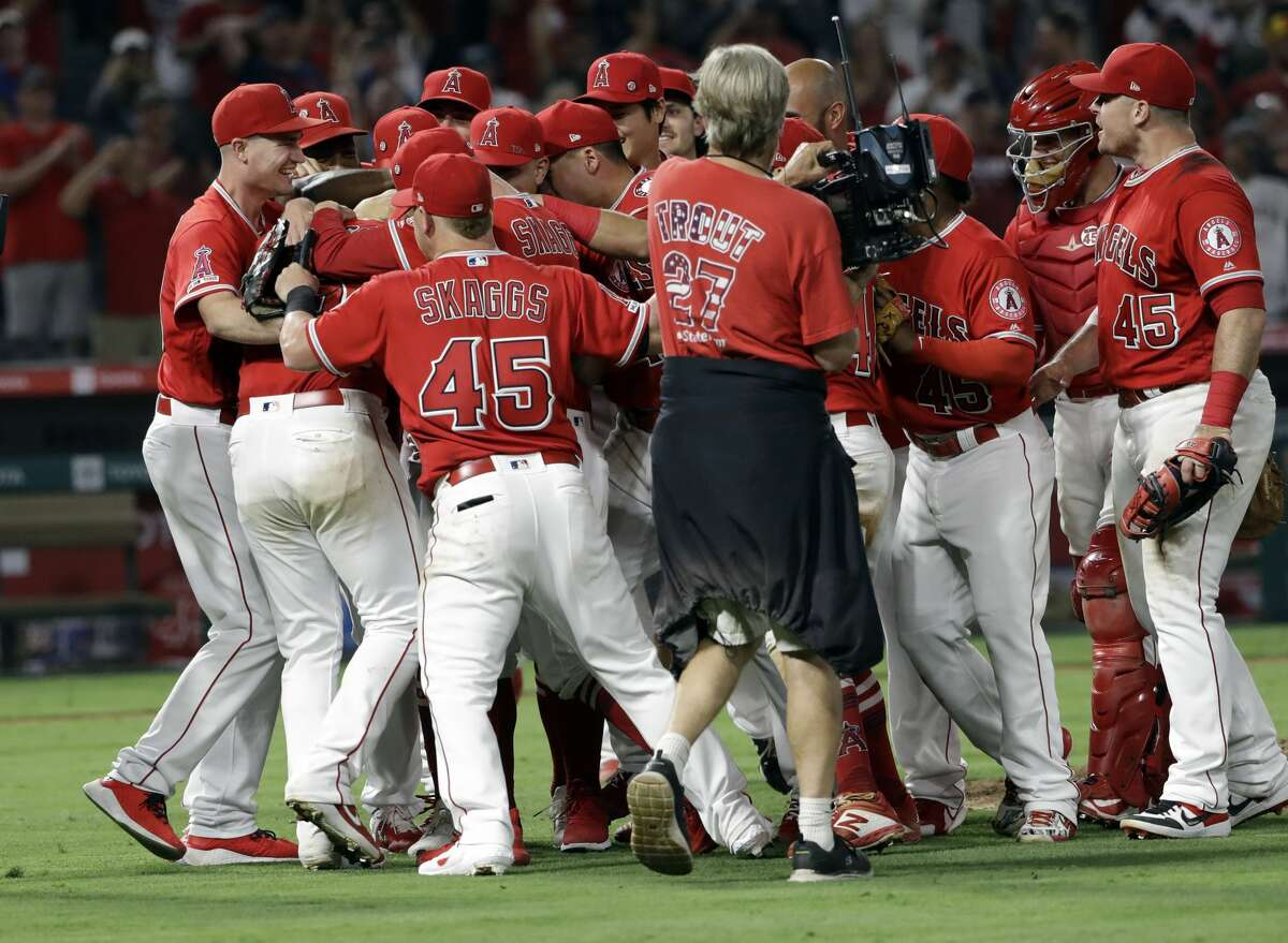 Los Angeles Angels relief pitcher Felix Pena, second from left, is congratulated by teammates after he finished off a combined no-hitter against the Seattle Mariners during a baseball game Friday, July 12, 2019, in Anaheim, Calif. Taylor Cole pitched the first two innings. (AP Photo/Marcio Jose Sanchez)