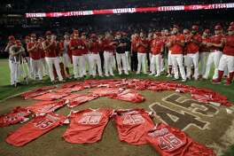 Members of the Los Angeles Angels place their jerseys with No. 45 in honor of pitcher Tyler Skaggs on the mound after a combined no-hitter against the Seattle Mariners during a baseball game Friday, July 12, 2019, in Anaheim, Calif. The Angels won 13-0. (AP Photo/Marcio Jose Sanchez)