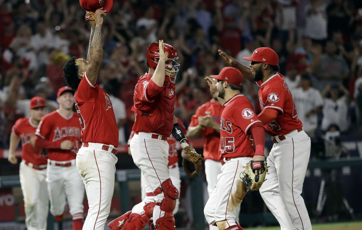 Los Angeles Angels relief pitcher Felix Pena, left, catcher Dustin Garneau, center, and teammates celebrate after a combined no-hitter against the Seattle Mariners during a baseball game Friday, July 12, 2019, in Anaheim, Calif. The Angels won 13-0. (AP Photo/Marcio Jose Sanchez)