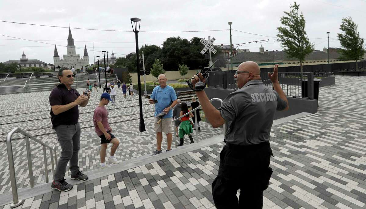 A security guard asks visitors to leave a closed area along the Mississippi River near Jackson Square, Friday, July 12, 2019, in New Orleans, ahead of Tropical Storm Barry. The National Weather Service in New Orleans says water is already starting to cover some low lying roads as Tropical Storm Barry approaches the state from the Gulf of Mexico.