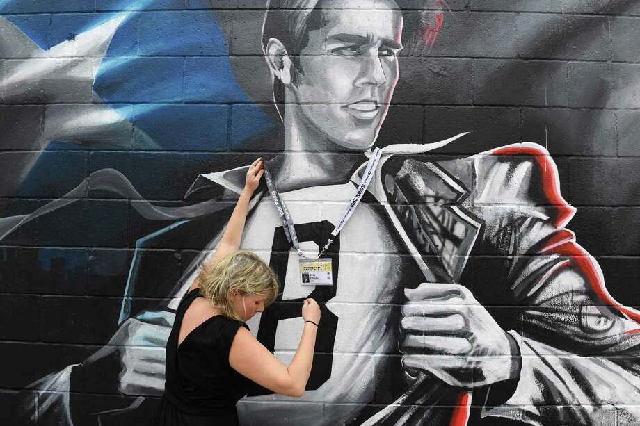 Katie Baron decorates a Beto O'Rourke mural with items from South by Southwest conference and festivals so she could take a photo on March 8, 2019, in Austin, Texas. Photo: Washington Post Photo By Matt McClain / The Washington Post