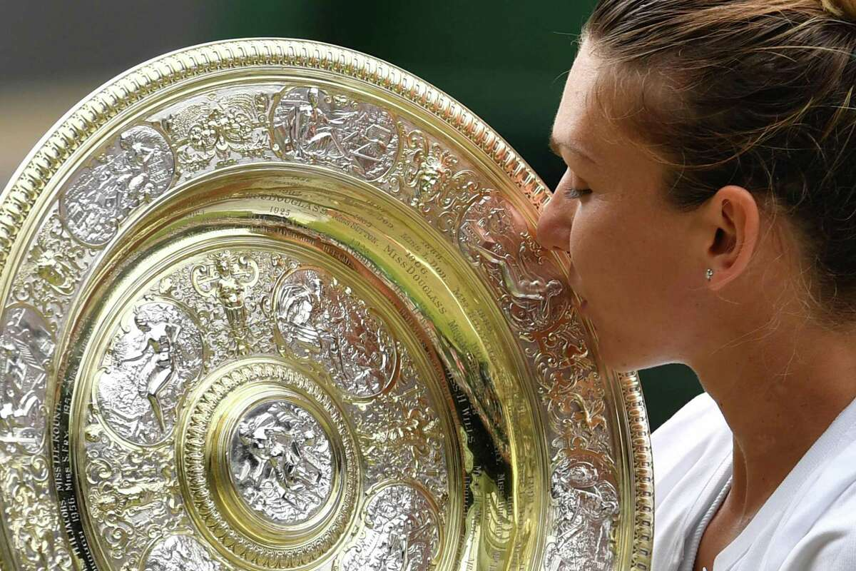 Romania's Simona Halep kisses the Venus Rosewater Dish trophy after beating US player Serena Williams during their women's singles final on day twelve of the 2019 Wimbledon Championships at The All England Lawn Tennis Club in Wimbledon, southwest London, on July 13, 2019. (Photo by GLYN KIRK / AFP) / RESTRICTED TO EDITORIAL USEGLYN KIRK/AFP/Getty Images