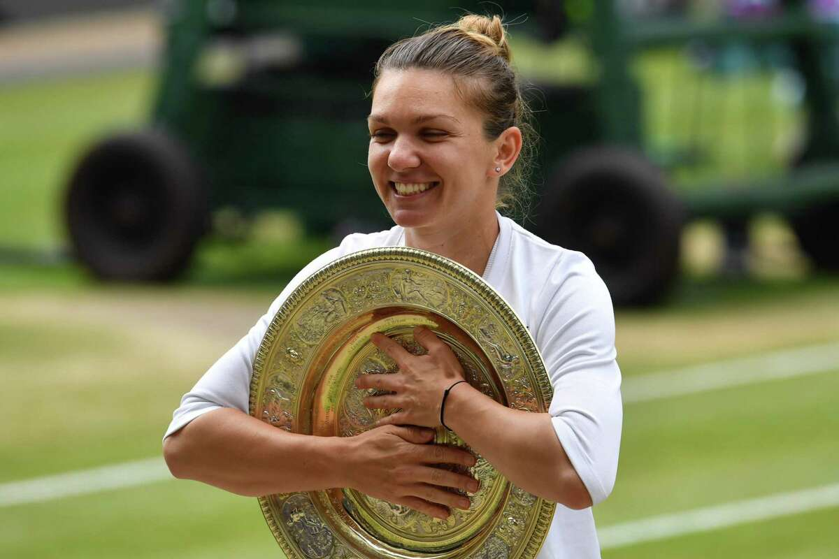 Romania's Simona Halep poses with the Venus Rosewater Dish trophy after beating US player Serena Williams during their women's singles final on day twelve of the 2019 Wimbledon Championships at The All England Lawn Tennis Club in Wimbledon, southwest London, on July 13, 2019. (Photo by GLYN KIRK / AFP) / RESTRICTED TO EDITORIAL USEGLYN KIRK/AFP/Getty Images