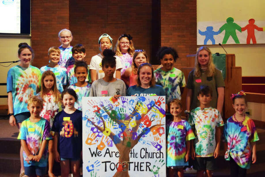 Volunteers and participants of Vacation Bible School at the First Christian Church showoff their art project that showcases all their handprints and growth in faith.