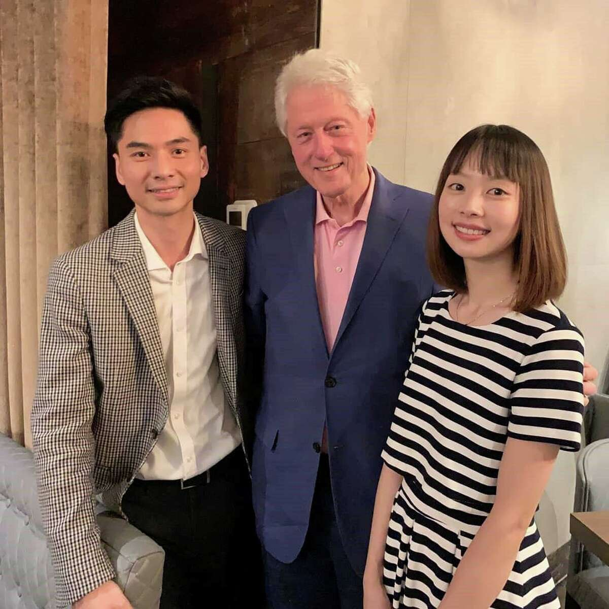 K Dong, owner of MIKU Sushi Bar and Restaurant at 62 Greenwich Ave., poses for a photo with President Bill Clinton and MIKU's hostess Coco on July 6.