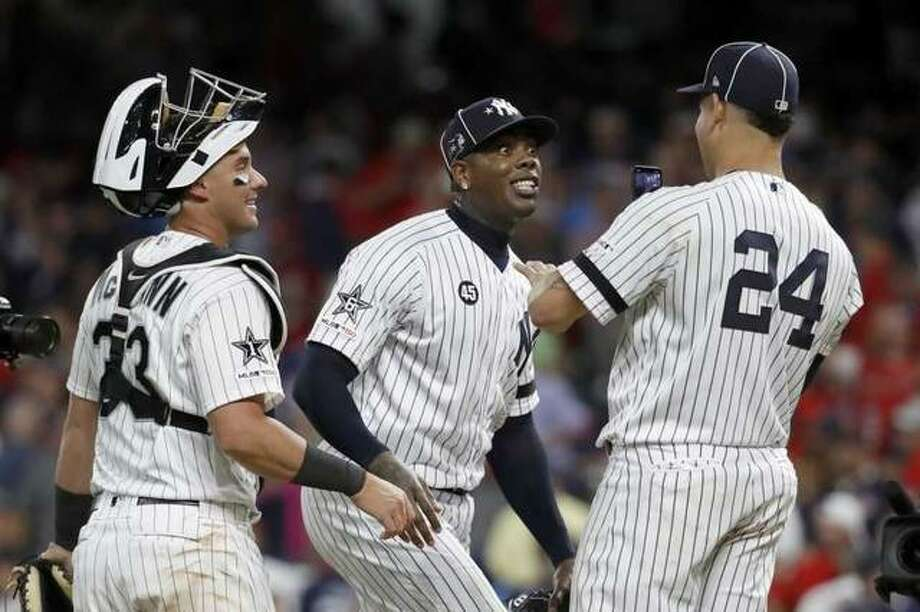 American League pitcher Aroldis Chapman, of the New York Yankees, jokes with teammate Gary Sanchez (24), of the New York Yankees, and James McCann, left, of the Chicago White Sox, after the American League defeated by National League 4-3 in the MLB baseball All-Star Game, Tuesday, July 9, 2019, in Cleveland.
