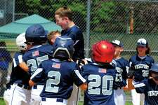 Westport's Charlie Leahy lands at the plate after a home run drive against Fairfield American in Saturday's District 2 Little League championship.