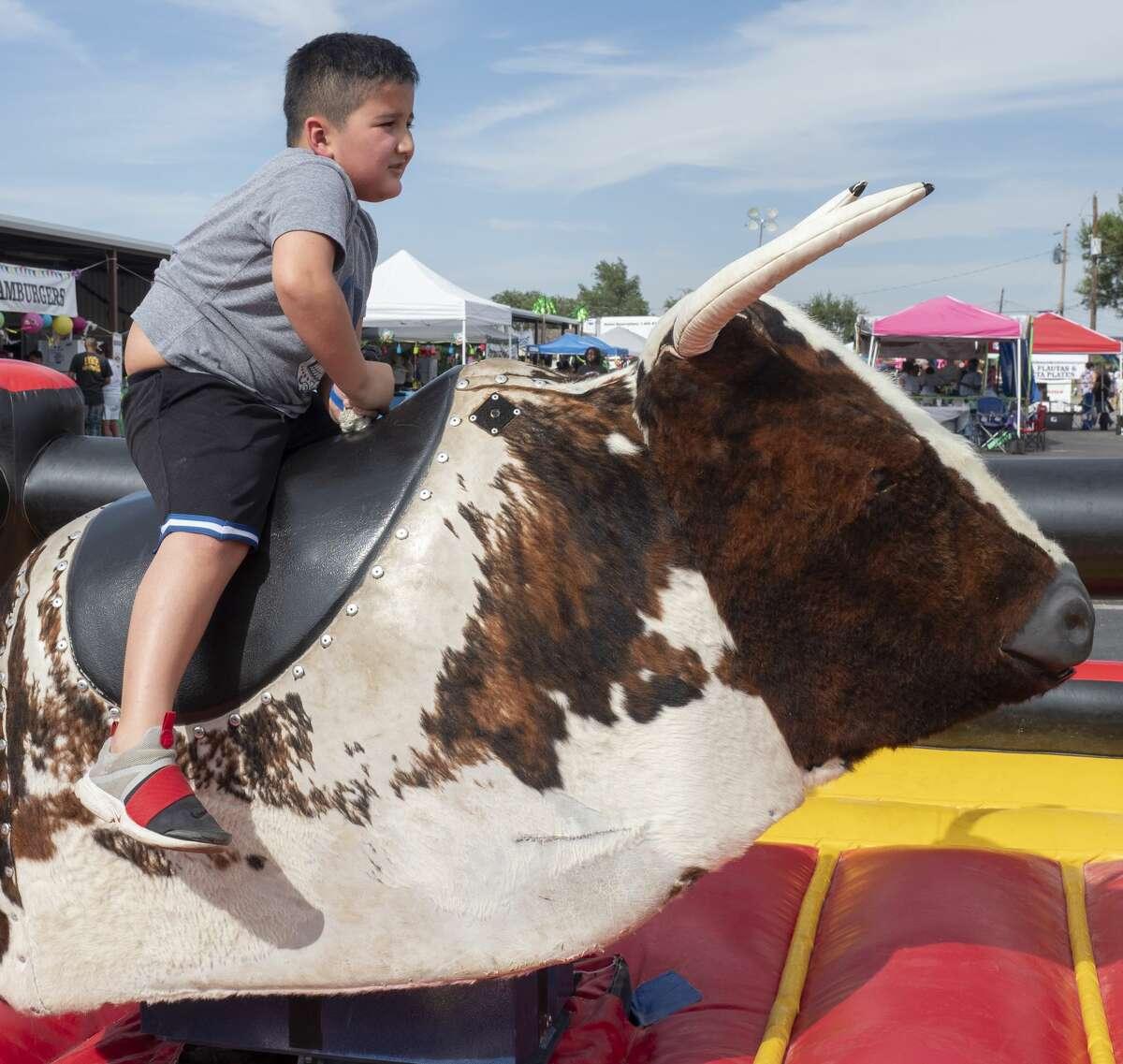 Lucas Garcia tries his luck at bull riding 07/13/19 at the 36th annual San Miguel Arcangel Family Fair. Tim Fischer/Reporter-Telegram
