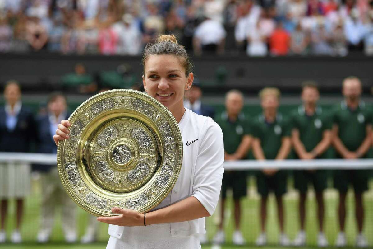 TOPSHOT - Romania's Simona Halep poses with the Venus Rosewater Dish trophy after beating US player Serena Williams during their women's singles final on day twelve of the 2019 Wimbledon Championships at The All England Lawn Tennis Club in Wimbledon, southwest London, on July 13, 2019. (Photo by Ben STANSALL / AFP) / RESTRICTED TO EDITORIAL USEBEN STANSALL/AFP/Getty Images