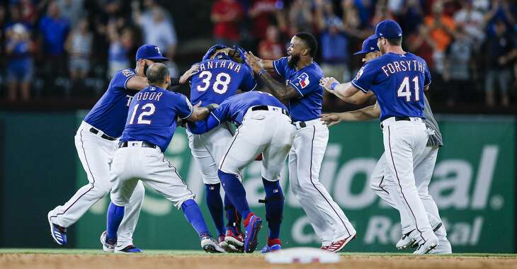 Texas Rangers' Danny Santana (38) is congratulated by teammates after hitting a walk-off single to end a baseball game against the Houston Astros, Friday, July 12, 2019, in Arlington, Texas. Texas won 9-8. (AP Photo/Brandon Wade)
