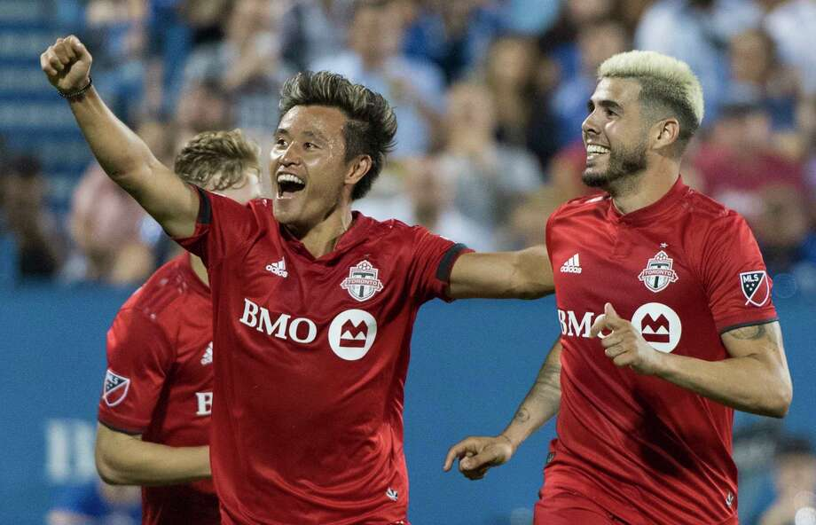 Toronto FC's Alejandro Pozuelo, right, celebrates with teammate Tsubasa Endoh after scoring during second-half MLS soccer match action against the Montreal Impact in Montreal, Saturday, July 13, 2019. (Graham Hughes/The Canadian Press via AP) Photo: Graham Hughes / The Canadian Press