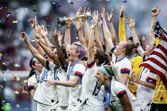 Megan Rapinoe, hoisting the trophy, leads the U.S. team in celebration after winning the Women's World Cup in France.