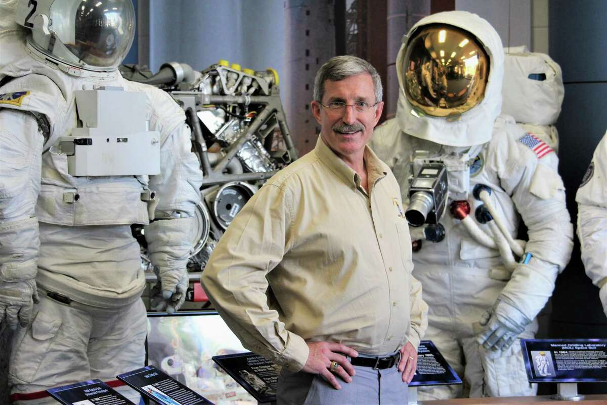 Dan Burbank, a retired astronaut from Tolland and now senior technical fellow at Collins Aerospace in Windsor Locks, part of United Technologies Corp., stands in a Collins lobby with a display of space suits and other systems developed by the company.