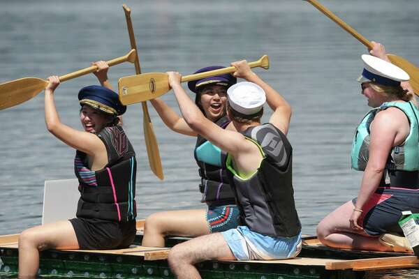 A group of Seafair interns celebrates the seaworthiness of their just built boat during the annual Seafair Milk Carton Derby, Saturday, July 13, 2019 at Green Lake.