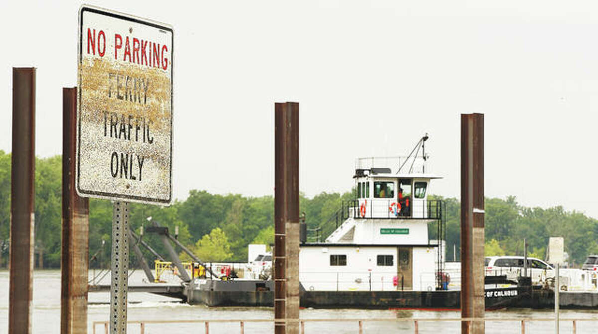 A sign as people enter the wait line for the ferry shows the high water mark of this year's flooding. The ferry was out of service for weeks, leaving a long drive to Joe Page Bridge in Hardin.