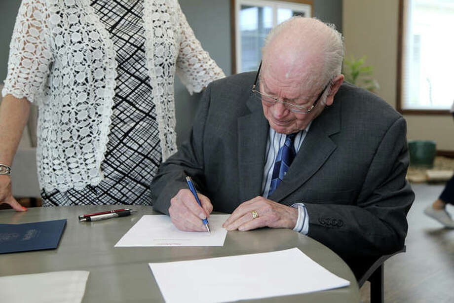 "Scott Long signs an agreement with MacMurray College to create the Elizabeth ""Betty"" Ingram Long Scholarship, which will be awarded annually to a nursing or education major at the college. Photo: Photo Provided"