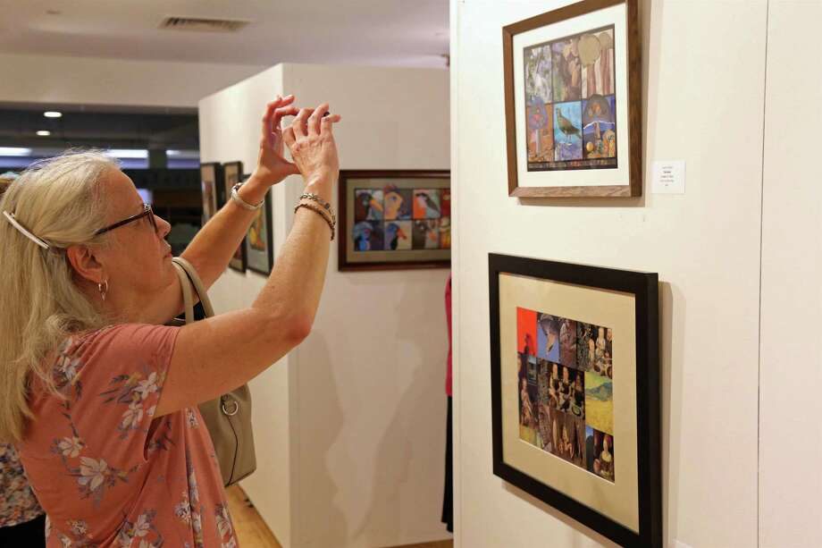 "MaryEllen Waleole of Easton grabs a phone shot of a piece at the opening reception for the show ""Diversity"" at the Bruce Kershner Gallery at Fairfield Library on Friday, July 12, 2019, in Fairfield, Conn. Photo: Jarret Liotta / Jarret Liotta / ©Jarret Liotta"
