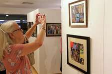 """MaryEllen Waleole of Easton grabs a phone shot of a piece at the opening reception for the show """"Diversity"""" at the Bruce Kershner Gallery at Fairfield Library on Friday, July 12, 2019, in Fairfield, Conn."""