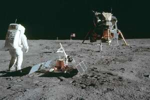 In this July 20, 1969 photo made available by NASA, astronaut Buzz Aldrin Jr. stands next to the Passive Seismic Experiment device on the surface of the the moon during the Apollo 11 mission.
