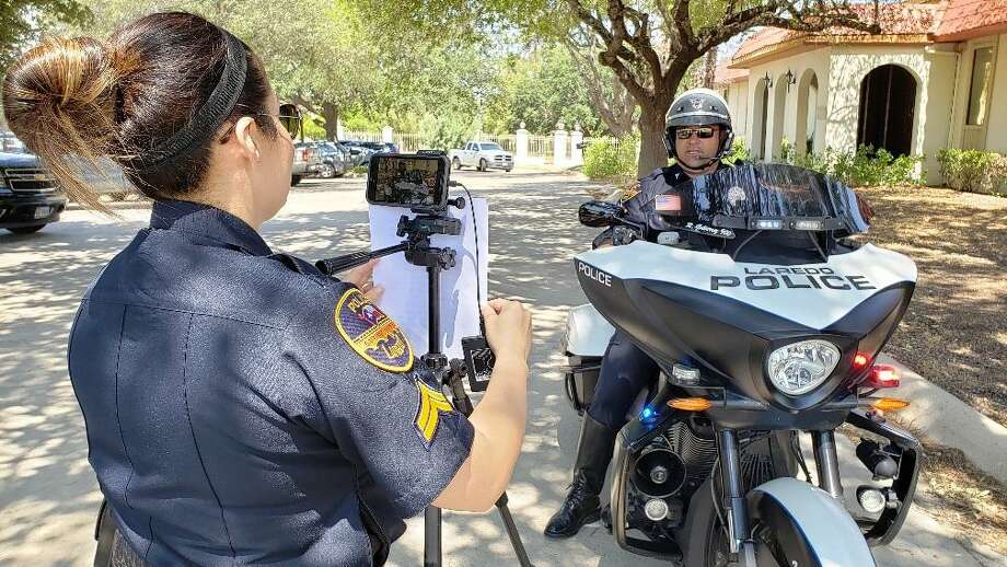 Investigator Gina G. Gonzales records Officer Ruben Gutierrez as he shares a traffic tip about yield signs. This is part of Motor Squad Monday, an initiative on traffic safety where the department addresses concerns from the community. Photo: César G. Rodriguez /Laredo Morning Times