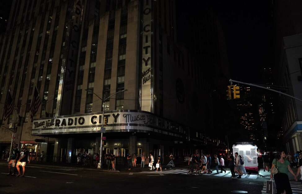 TOPSHOT - People walk past Radio City Music Hall in the dark during a major power outage affecting parts of New York City on July 13, 2019. - Subway stations plunged into darkness and the billboards of Times Square suddenly flicked off as New York's Manhattan was hit by a power outage on Saturday. About 42,000 customers lost electricity in the early evening, according to the Con Edison utility, which did not give a reason for the cut. (Photo by TIMOTHY A. CLARY / AFP)TIMOTHY A. CLARY/AFP/Getty Images