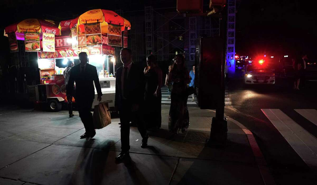 TOPSHOT - People walk down the streets during a major power outage affecting parts of New York City on July 13, 2019. - Subway stations plunged into darkness and the billboards of Times Square suddenly flicked off as New York's Manhattan was hit by a power outage on Saturday. About 42,000 customers lost electricity in the early evening, according to the Con Edison utility, which did not give a reason for the cut. (Photo by TIMOTHY A. CLARY / AFP)TIMOTHY A. CLARY/AFP/Getty Images