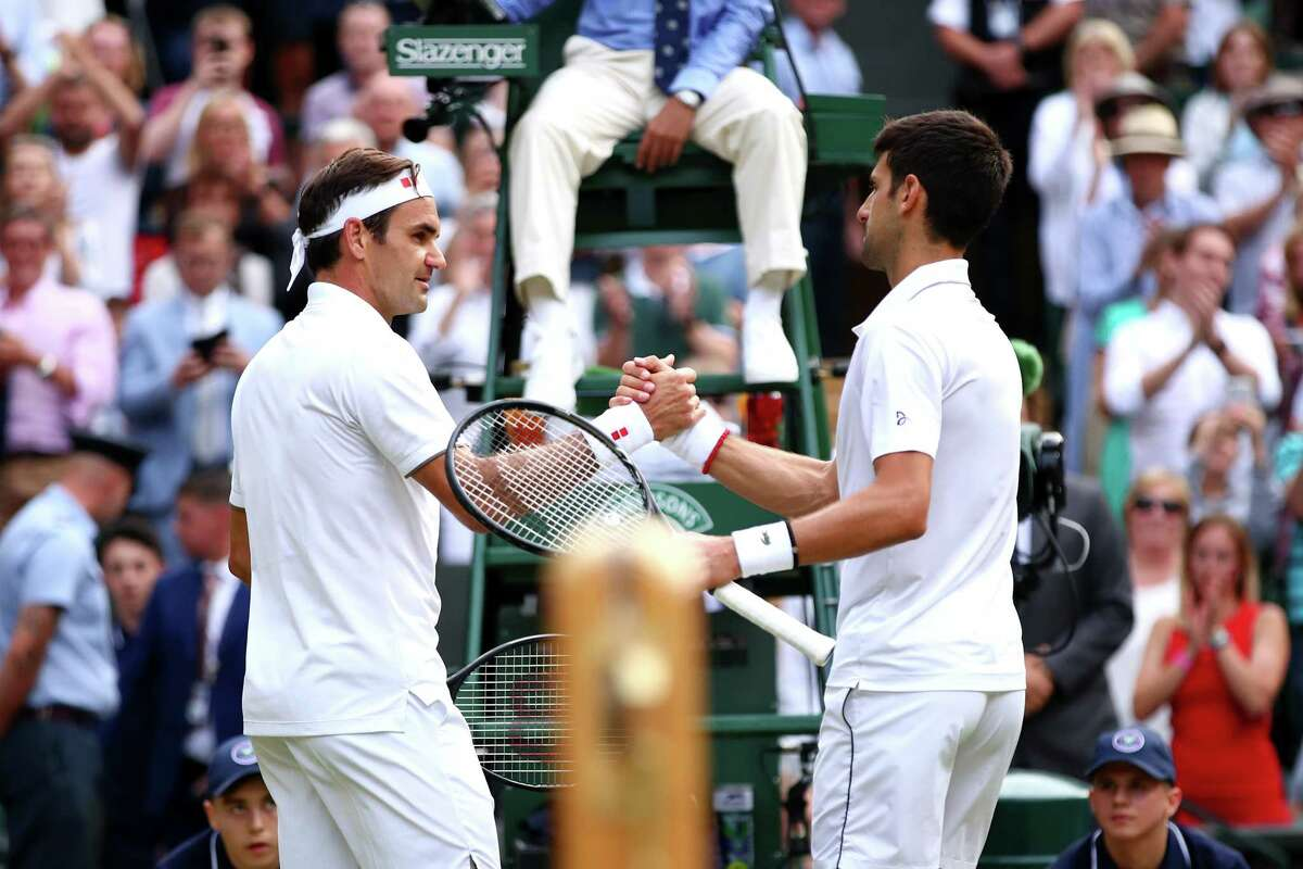 LONDON, ENGLAND - JULY 14: Novak Djokovic of Serbia shakes hands at the net with Roger Federer of Switzerland following victory in his Men's Singles final during Day thirteen of The Championships - Wimbledon 2019 at All England Lawn Tennis and Croquet Club on July 14, 2019 in London, England.