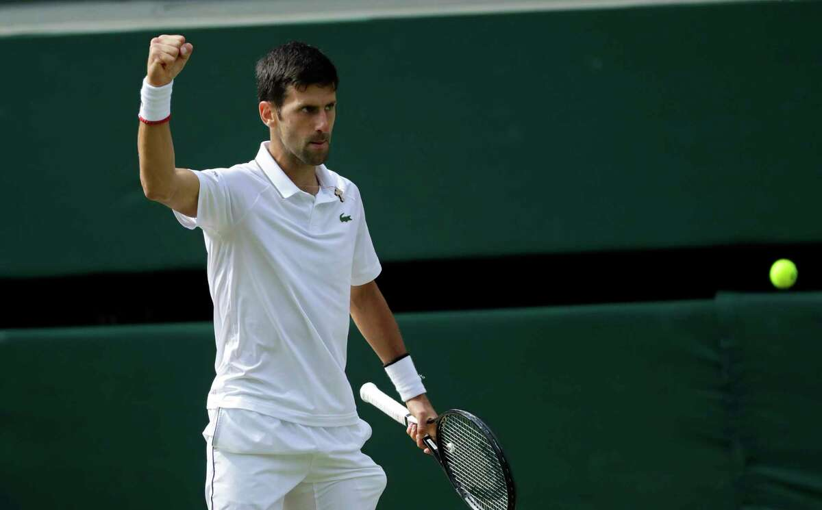 Serbia's Novak Djokovic reacts after scoring a point in the 3rd set tiebreak with Switzerland's Roger Federer during the men's singles final match of the Wimbledon Tennis Championships in London, Sunday, July 14, 2019.