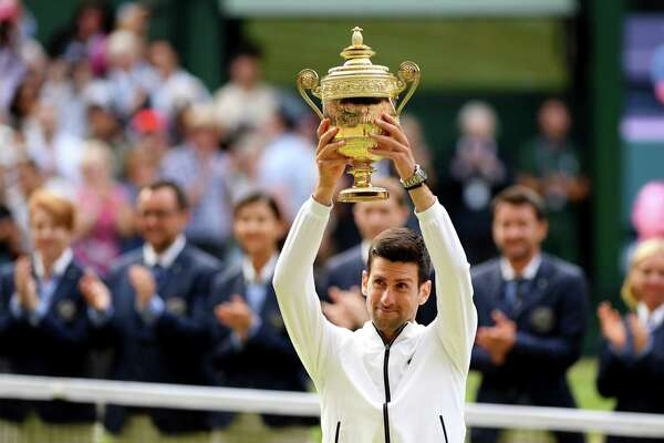 LONDON, ENGLAND - JULY 14: Novak Djokovic of Serbia lifts the trophy after winning his Men's Singles final against Roger Federer of Switzerland during Day thirteen of The Championships - Wimbledon 2019 at All England Lawn Tennis and Croquet Club on July 14, 2019 in London, England.