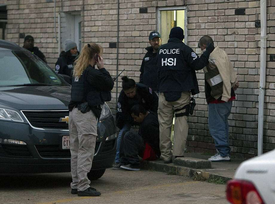 In this file photo, police arrest suspected undocumented employees after raiding a business in Southwest Houston. Photo: Cody Duty, Houston Chronicle