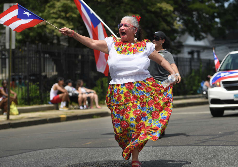 Milagros Ortiz, of New Britain, dances her way down Park Avenue during the annual Puerto Rican Day Parade in Bridgeport, Conn. on Sunday, July 14, 2019. Photo: Brian A. Pounds, Hearst Connecticut Media / Connecticut Post