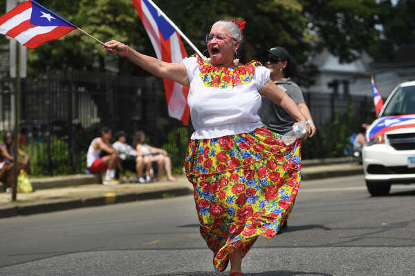 Milagros Ortiz, of New Britain, dances her way down Park Avenue during the annual Puerto Rican Day Parade in Bridgeport, Conn. on Sunday, July 14, 2019.