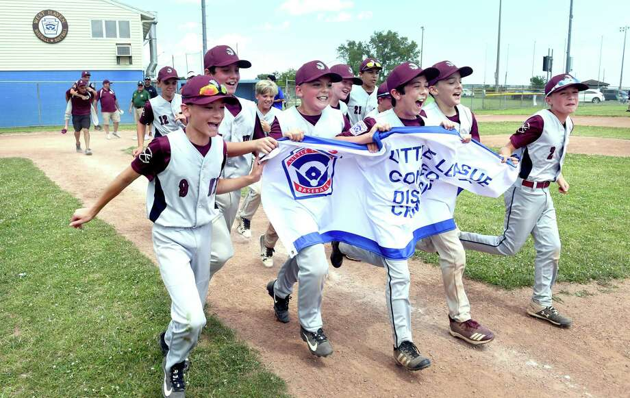 Members of the North Haven Little League team celebrate after defeating Milford to win the District 4 championship in West Haven on Sunday. Photo: Arnold Gold / Hearst Connecticut Media / New Haven Register