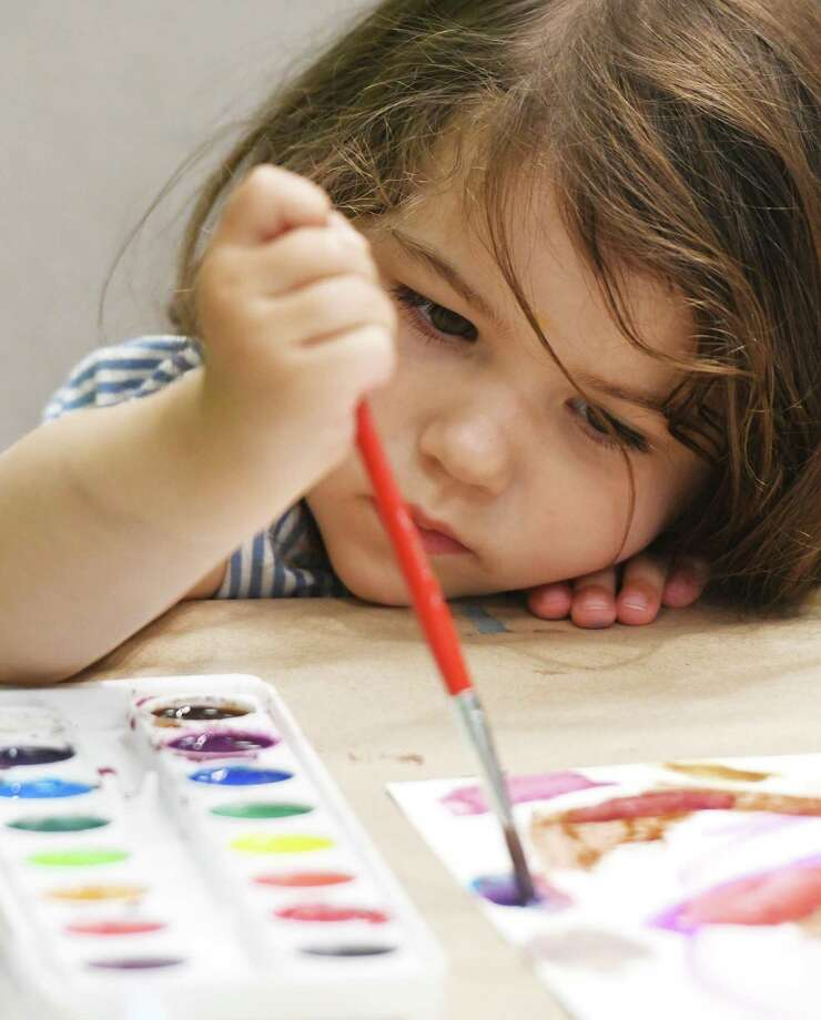 """Greenwich's Carter Shaw, 2, paints in watercolors at the """"Bruce Creates"""" workshop during Summer Family Day at the Bruce Museum in Greenwich, Conn. Sunday, July 14, 2019. With """"Sharks!"""" and """"Summer with the Averys"""" on display, visitors learned about sharks, including live baby sharks, and created postcards just as the Avery family did during their summer trips. Additionally, the Bruce's artist in residence Milena Alvarez, a 21-year-old Colombian-American student based in Norwalk, ran the """"Bruce Creates"""" watercolor workshop for both kids and adults. Photo: Tyler Sizemore / Hearst Connecticut Media / Greenwich Time"""