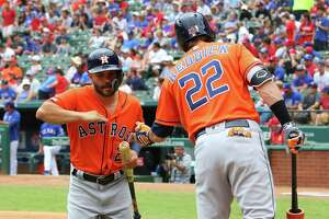 ARLINGTON, TX - JULY 14: Josh Reddick #22 of the Houston Astros congratulates Jose Altuve #27 for scoring in the first inning against the Texas Rangers at Globe Life Park in Arlington on July 14, 2019 in Arlington, Texas.
