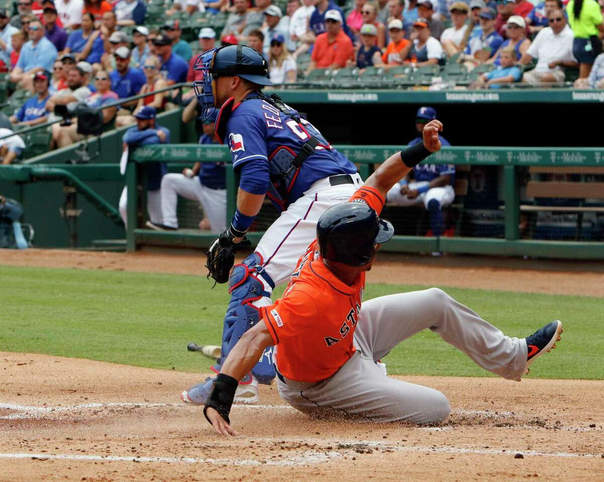 Houston Astros' Michael Brantley, right, scores ahead of the throw to Texas Rangers catcher Tim Federowicz in the first inning of a baseball game against the Texas Rangers, Sunday, July 14, 2019, in Arlington, Texas. (AP Photo/David Kent)