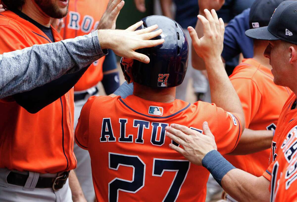 Houston Astros' Jose Altuve (27) is congratulated by teammates in the dugout after scoring on Yordan Alvarez's single in the first inning of a baseball game against the Texas Rangers, Sunday, July 14, 2019, in Arlington, Texas. (AP Photo/David Kent)