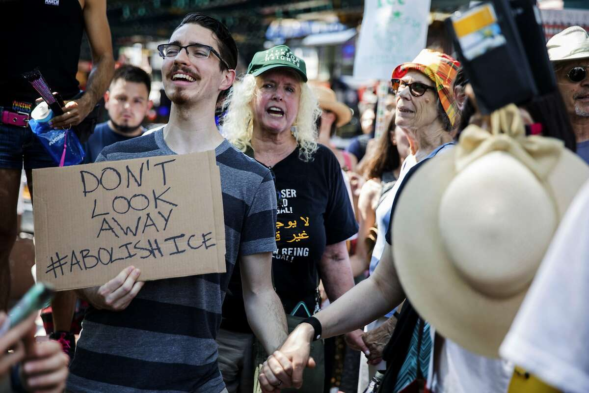 People holds hands as they chant at a rally before the start of a march in opposition to the Trump administration's plans to continue with raids to catch immigrants in the country illegally, Sunday, July 14, 2019, in the Queens borough of New York. (AP Photo/Julius Constantine Motal)