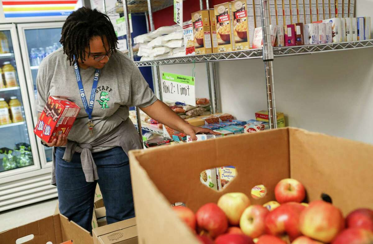 Chelsea Markcray, a student worker, stocks food from a new delivery at a free market at the University of Houston-Downtown campus on Tuesday, May 14, 2019, in Houston.