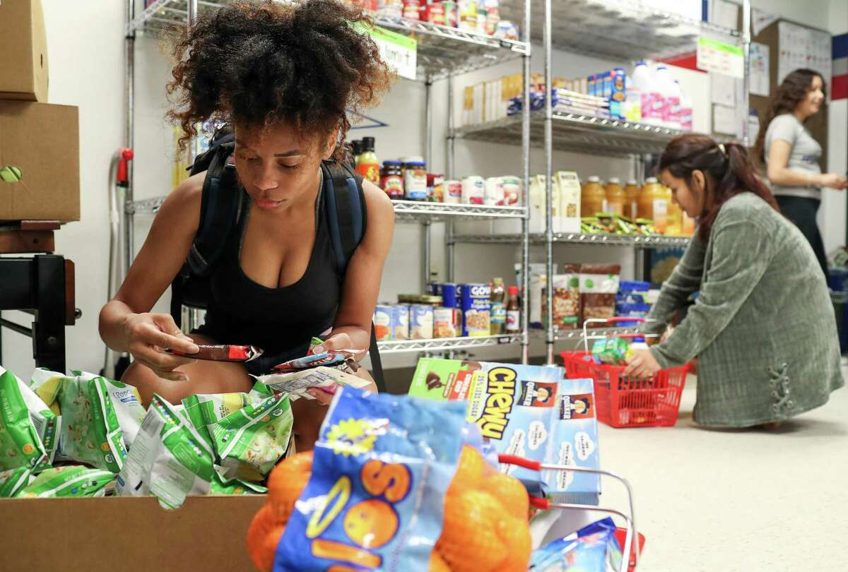 Shey-Marie Posey, a biology student, looks for groceries at a free market at the University of Houston-Downtown campus on Tuesday, May 14, 2019 in Houston. Posey said the food goes to her and five other people in her household, because otherwise she can only spend about $300 per month on food.