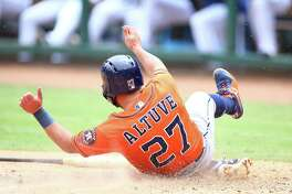 Jose Altuve (27) of the Houston Astros slides in safe at home in the second inning against the Texas Rangers at Globe Life Park in Arlington on July 14, 2019 in Arlington, Texas.