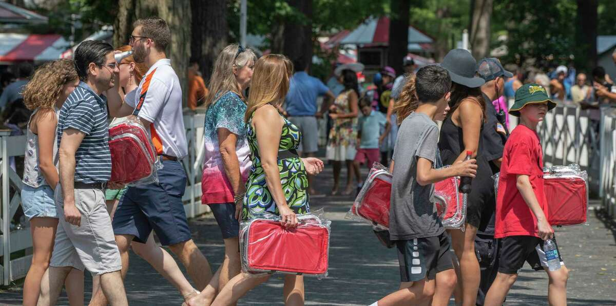 Race patrons carry arm loads of the Saratoga Cooler on premium day at the Saratoga Race Course Sunday July 14, 2019 in Saratoga Springs, N.Y. Special to the Times Union by Skip Dickstein