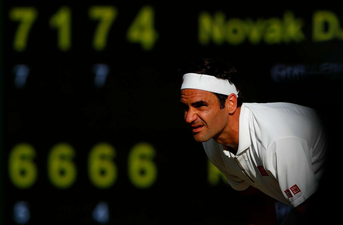 Switzerland's Roger Federer prepares to return against Serbia's Novak Djokovic during their men's singles final on day thirteen of the 2019 Wimbledon Championships at The All England Lawn Tennis Club in Wimbledon, southwest London, on July 14, 2019. (Photo by Adrian DENNIS / POOL / AFP) / RESTRICTED TO EDITORIAL USEADRIAN DENNIS/AFP/Getty Images