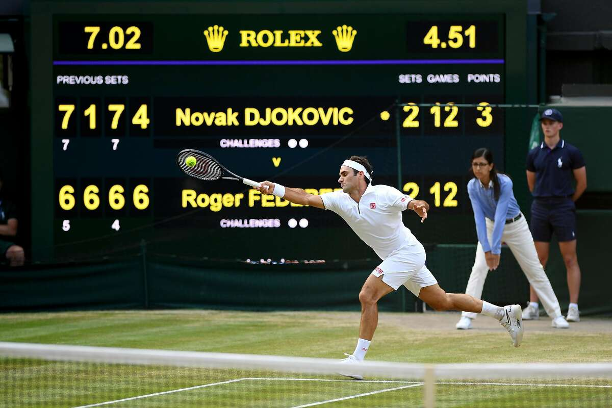 LONDON, ENGLAND - JULY 14: The scoreboard is seen as Roger Federer of Switzerland plays a forehand in the final set in the Men's Singles final between Novak Djokovic of Serbia and Roger Federer of Switzerland during Day thirteen of The Championships - Wimbledon 2019 at All England Lawn Tennis and Croquet Club on July 14, 2019 in London, England. (Photo by Matthias Hangst/Getty Images)