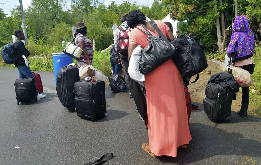 Men and women wait to cross the border at the end of Roxham Road in Champlain, N.Y. The rural roadway is attracting migrants from around the country who plan to leave the United States to seek political asylum in Canada. (Chris Churchill / Times Union)