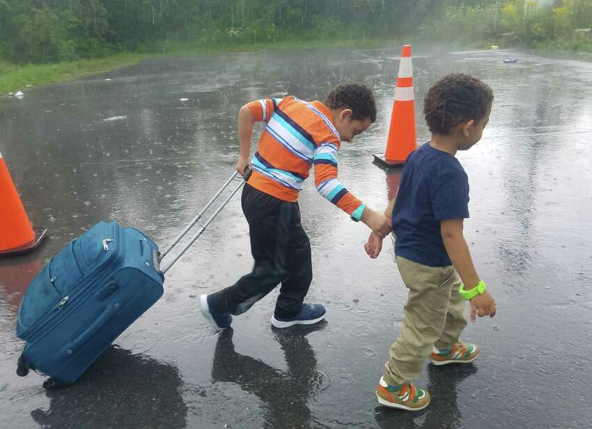 In pouring rain, two young boys make their way toward the illegal border crossing at the end of Roxham Road in Champlain, N.Y. The rural roadway is attracting migrants from around the country who plan to leave the United States to seek political asylum in Canada. (Chris Churchill / Times Union) ORG XMIT: MER2017081715154255