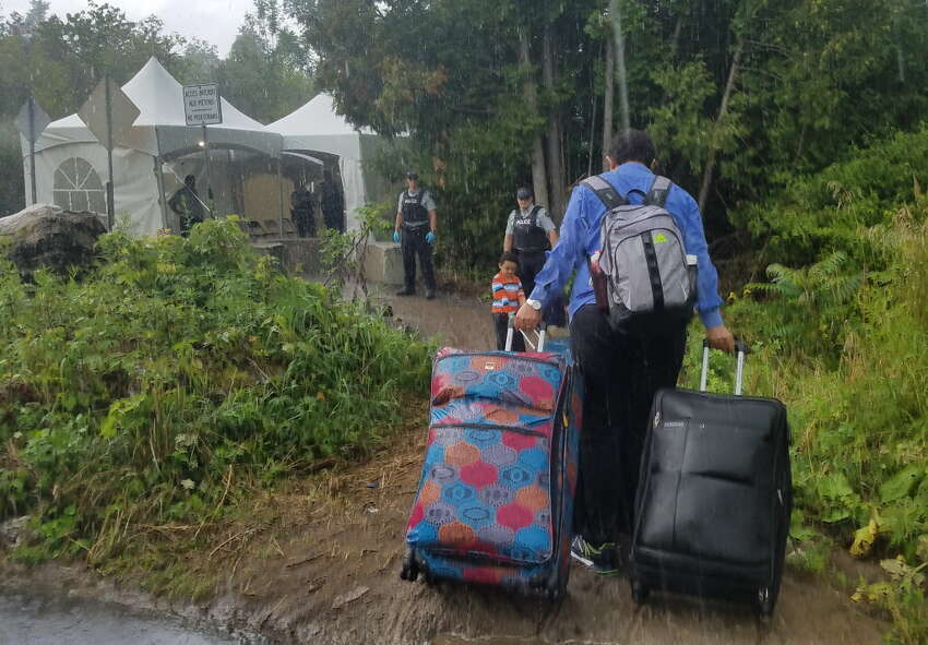 In pouring rain, a family leaves the United States for Canada at the end of Roxham Road in Champlain, N.Y. The rural roadway is attracting migrants from around the country who plan to leave the United States to seek political asylum in Canada. (Chris Churchill / Times Union) ORG XMIT: MER2017081715165065